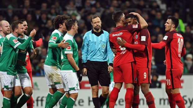 epa07322795 Bremen players (L) argue with referee Markus Schmidt (C) as Frankfurt's Sebastien Haller (2-R) celebrates with his teammates after scoring the 2-2 equalizer from the penalty spot during the German Bundesliga soccer match between SV Werder Bremen and Eintracht Frankfurt in Bremen, Germany, 26 January 2019.  EPA/DAVID HECKER CONDITIONS - ATTENTION: The DFL regulations prohibit any use of photographs as image sequences and/or quasi-video.