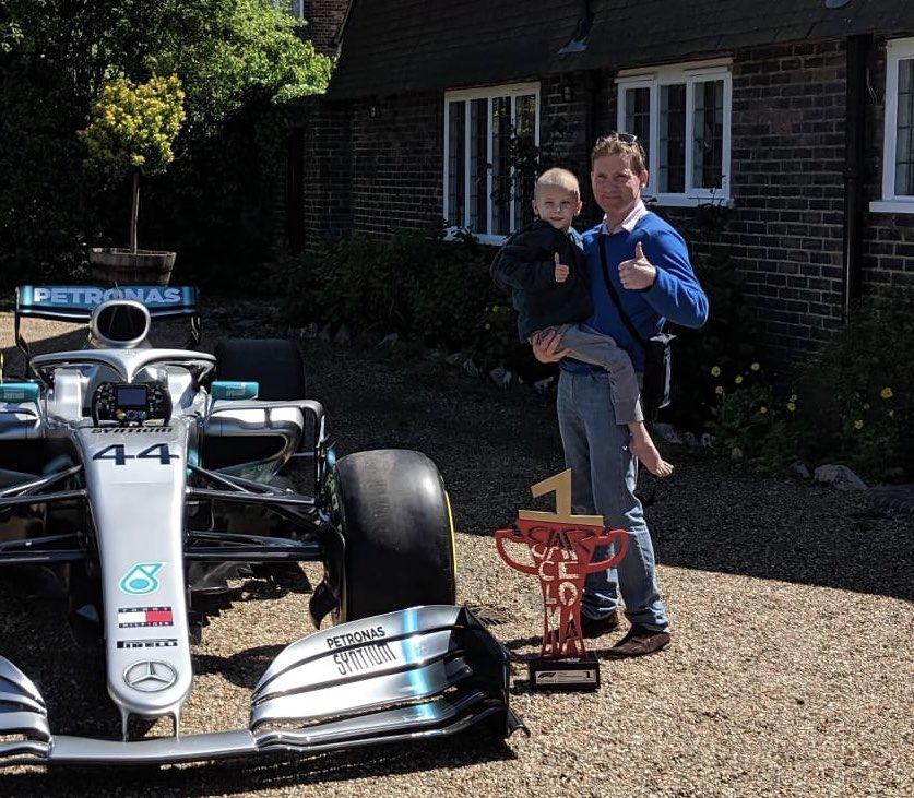 Harry és édesapja Lewis Hamilton autójával és barcelonai győzelmi trófeájával (Fotó: Harry Shaw/Twitter)